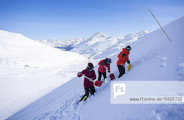 Die Profi-Snowboarder Robin Van Gyn  Marie France Roy und Helen Schettini demonstrieren an einem sonnigen Tag in Haines  Alaska  die richtige Schaufeltechnik für eine Lawinenrettung.