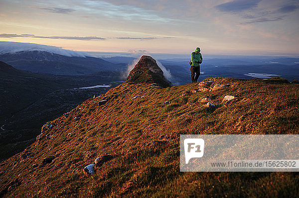 A hiker  photographer walks the summit of The Suilven mountain in Scotland  United Kingdom.