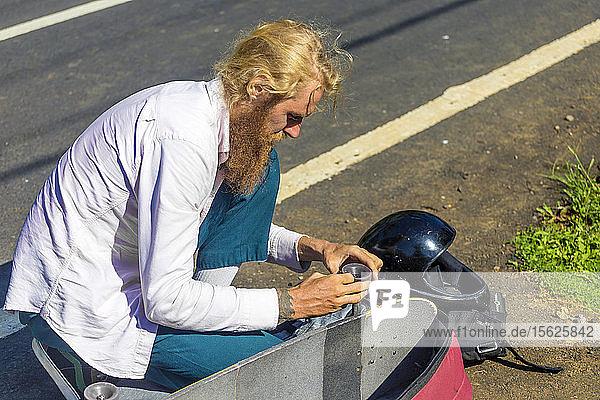 Longboarder bereitet sein Brett für den Einsatz vor