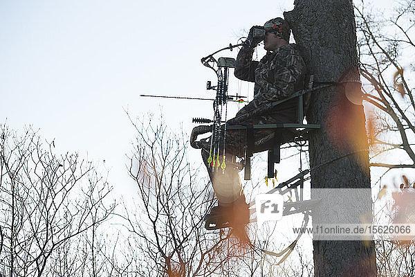 Junger erwachsener männlicher Jäger  der auf einem Baum sitzt und nach Rehen Ausschau hält