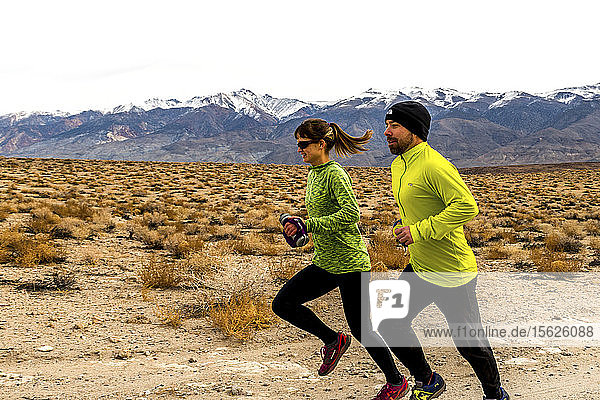 Man and woman out for a trail run on the Table Lands in Inyo County