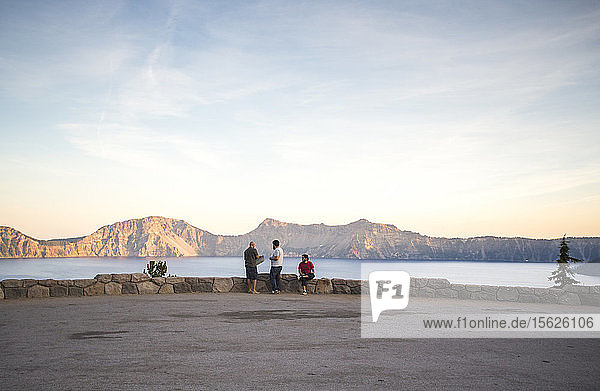 Distant view of three young men sit on a short rock wall overlooking at a giant mountain lake at sunset  Crater Lake  Oregon  USA