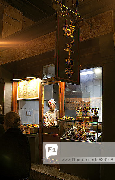Vendor in chefs hat at food shop at night market  Beijing  China