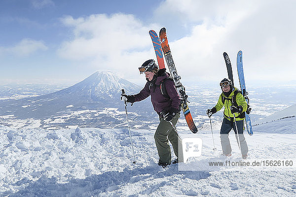 With the volcano Yotei in the background a female and male backcountry skier are hiking to the summit of mount Annupuri  near ski resort Niseko United on the Japanese island of Hokkaido. The skis they carry on their backpack are big and wide allowing the winter enthusiasts to fully enjoy skiing down the waist deep powder slopes Niseko United is known for. Niseko United is comprised of four resorts on the one mountain  Annupuri (1 308m). 100km south of Sapporo  Niseko Annupuri is a part of the Niseko-Shakotan-Otaru Kaigan Quasi-National Park and is the most eastern park of the Niseko Volcanic Group. Hokkaido  the north island of Japan  is geographically ideally located in the path of consistent weather systems that bring the cold air across the Sea of Japan from Siberia. This results in many of the resorts being absolutely dumped with powder that is renowned for being incredibly dry. Some of the Hokkaido ski resorts receive an amazing average of 14-18 meters of snowfall annually. Niseko is the powder capital of the world and as such is the most popular international ski destination in Japan. It offers an unforgettable experience for all levels of skier and snowboarder. Mount Yotei in the background is often referred to as the Mount Fuji of Hokkaido.