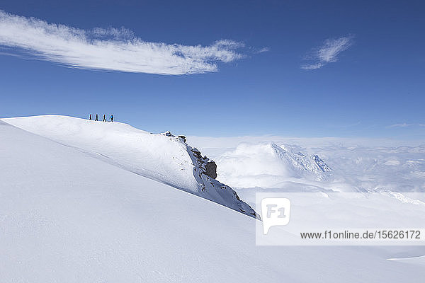 Mountaineers are walking over a snow ridge to the edge of the world  a feature near high camp on Denali in Alaska.