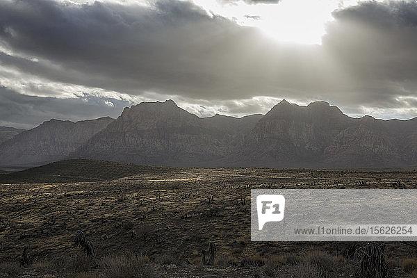 Sturmwolken ziehen über den Red Rock State Park und werfen Lichtstrahlen auf die Wüstenlandschaft.