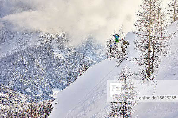 A man jumps down from a rock in the wood  during a cloudy ski morning in San Martino di Castrozza in the Dolomites