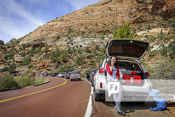 Smiling female hiker sitting in car trunk and looking at camera  Zion National Park  Utah  USA