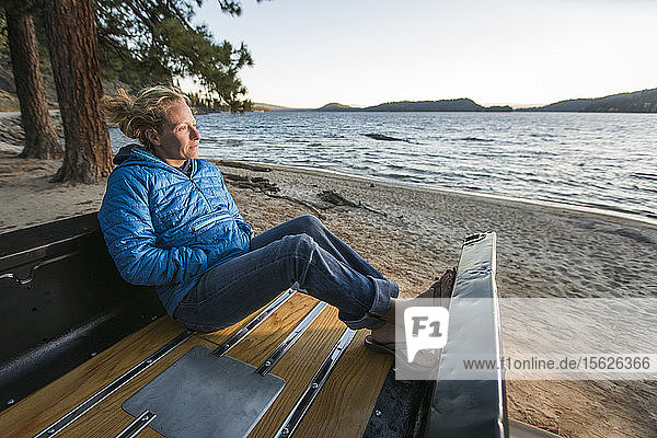 Woman sitting in renovated truck watching sunset along sheltered beach on Payette Lake in McCall  Idaho  USA