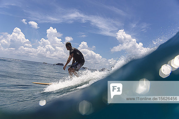 Male surfer riding wave against clouds  Male  Maldives