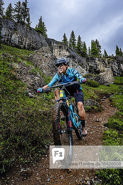 Portrait of Woman mountain biker rides downhill in scenic landscape on the Ice Lakes trail  USA