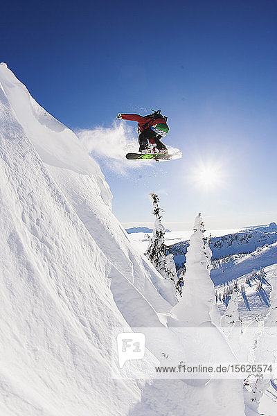 Snowboarder performing a 180 jump while snowboarding  Revelstoke  British Columbia  Canada