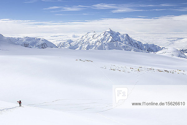 A ski mountaineer on his way on Denali in Alaska  with 14.000 feet camp visible in the background.