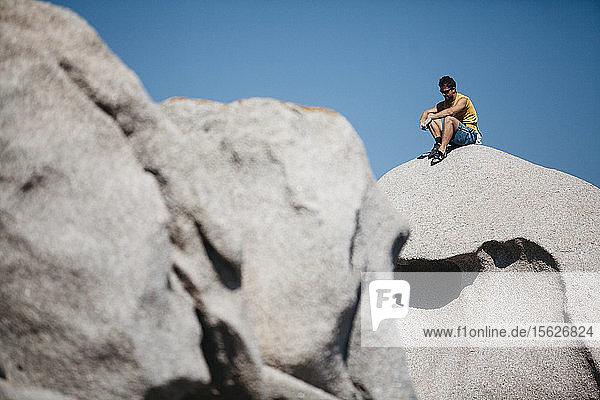 Man climbing on rock near sea  Capo��Testa  Sardinia  Italy