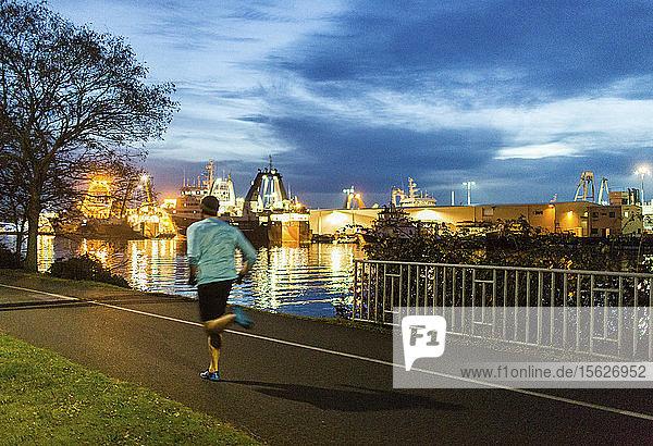 Mann joggt bei Sonnenuntergang entlang der Uferpromenade  Seattle  Washington State  USA