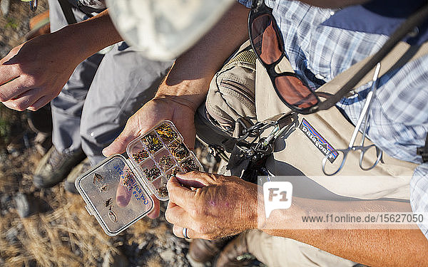 A Man Choosing A Fly From Fly Box While Fishing On Big Wood River In Ketchum  Idaho
