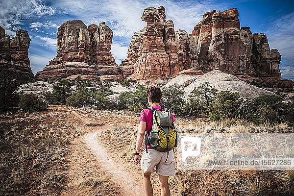 Rear view of a female hiker walking among the unusual sandstone formations in the Canyonlands National Park.