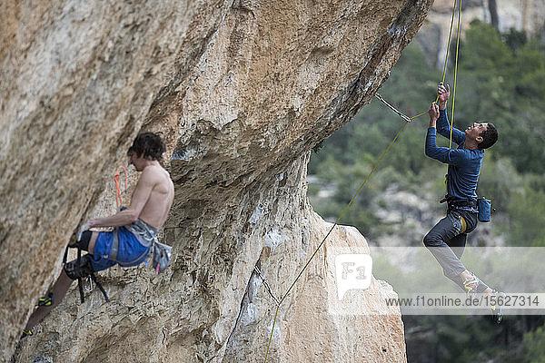 Side view of two adventurous men rock climbing  Siurana  Catalonia  Spain