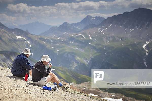 Two hikers is are having lunch on the ridge of the Tete des Fours with Mont Blanc valley in the distance. This is halfway the Tour du Mont Blanc  a classic multi day hike around the highest peak of the Alps.