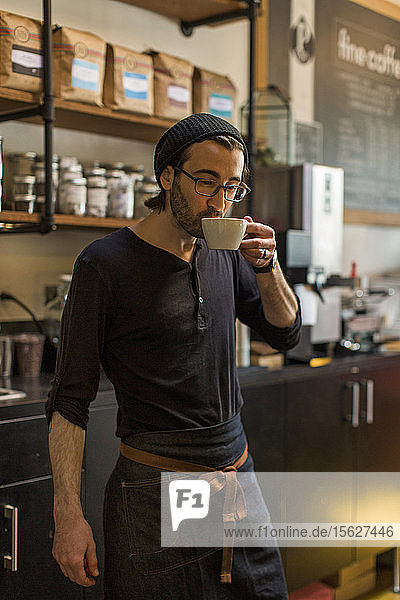 Maleï¾baristaï¾drinking coffee at cafe  Seattle  Washington  USA