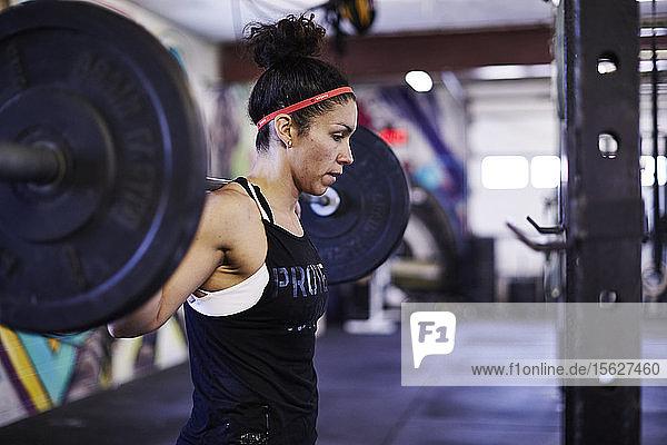 Frau arbeitet im Crossfit-Fitnessstudio