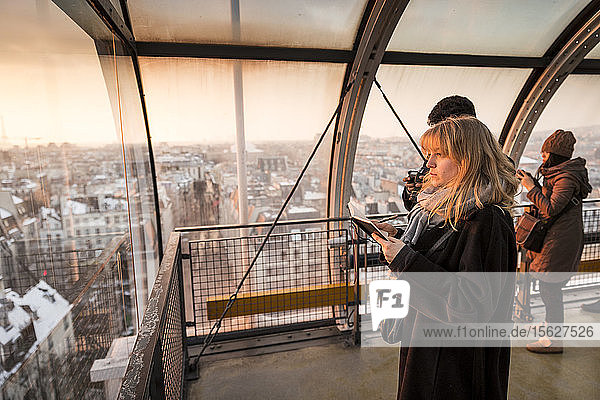 Tourists looking through window at view of Paris  France in Centre Georges Pompidou at sunset