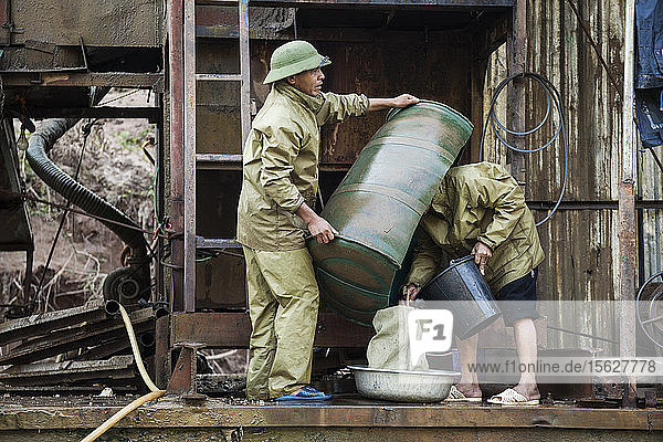 Vietnamese men empty out concentrate from the sluice box into a bag for later processing on the deck of a mechanical gold dredge floating on the Nam Ou River  Laos.