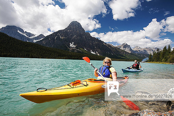 A Canadian couple kayaking on Waterfowl Lake in the Canadian Rockies.