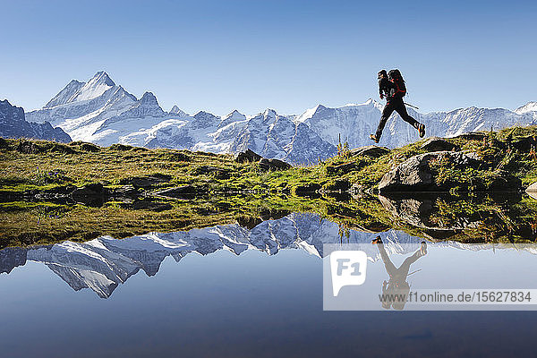 A hiker is jumping while his action posture is being reflected in a mountain lake above Grindelwald in the Swiss Alps. The famous Bernese Oberland peaks are in the background.