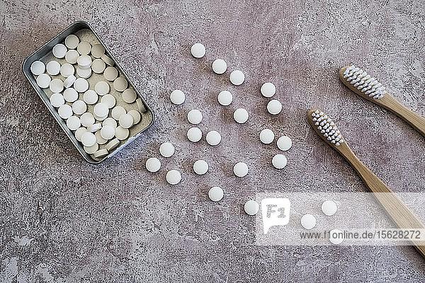 Nahaufnahme von zwei hölzernen Zahnbürsten und Pillen in einer Metallbox. Nahaufnahme von zwei hölzernen Zahnbürsten und Pillen in einer Metallbox.