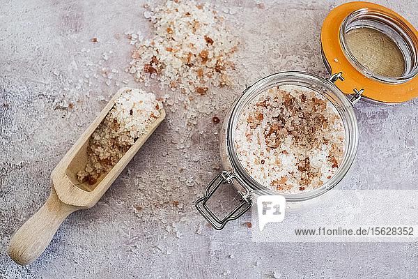 Hochwinkel-Nahaufnahme eines Holzlöffels und eines Glasgefäßes mit grobem Salz. Hochwinkel-Nahaufnahme eines Holzlöffels und eines Glasgefäßes mit grobem Salz.