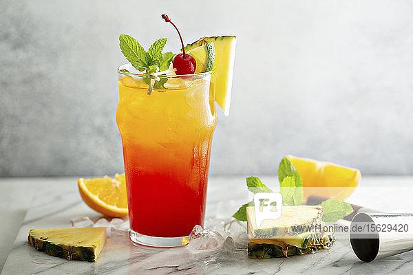 Tequila Sunrise mit Ananas und Orange als Deko