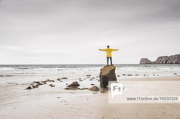 Junger Mann in gelber Regenjacke am Strand und auf Felsen stehend  Bretagne  Frankreich