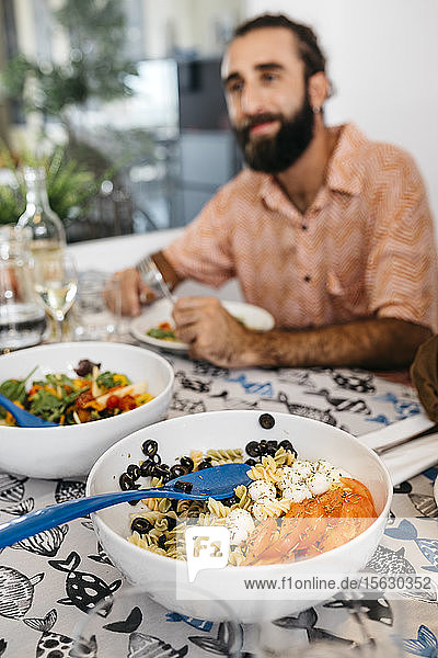 Smiling man sitting at dining table having healthy lunch