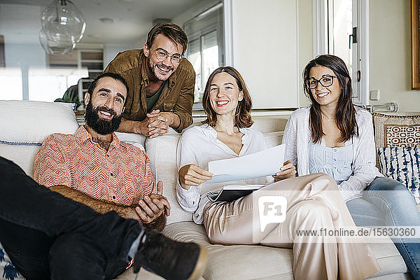 Portrait of happy friends sitting on couch with papers