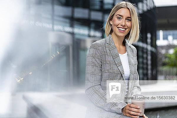 Porträt einer glücklichen jungen Geschäftsfrau mit Kaffee zum Mitnehmen in der Stadt