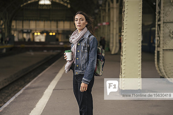 Junge weibliche Reisende mit Kaffee zum Mitnehmen auf den Bahnsteig