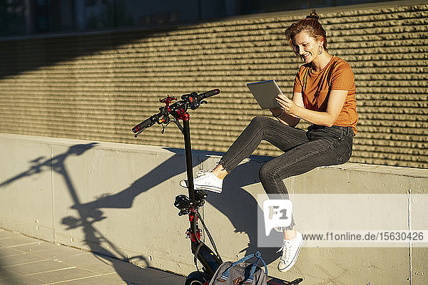 Smiling woman with electric scooter sitting on a wall at sunlight  using digital tablet
