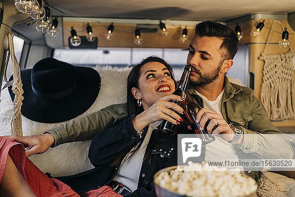 Glückliches junges Paar klirrende Bierflaschen im Wohnmobil