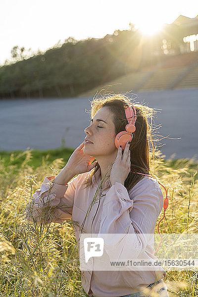 Porträt einer jungen Frau mit geschlossenen Augen  die im Freien mit Kopfhörern Musik hört