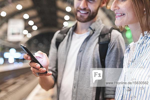 Junges Paar wartet am Bahnhof auf den Zug und benutzt ein Smartphone  Berlin  Deutschland