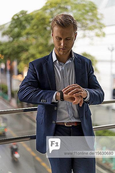 Junger Geschäftsmann überprüft die Zeit auf der Fußgängerbrücke