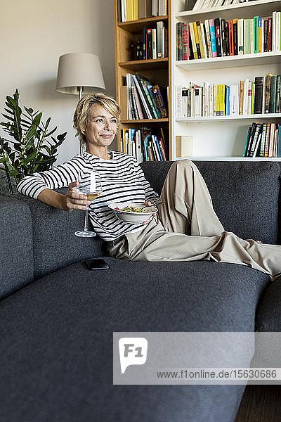 Reife Frau isst zu Hause hausgemachte Nudelgerichte und trinkt Wein auf der Couch