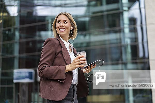 Glückliche junge Geschäftsfrau in der Stadt unterwegs