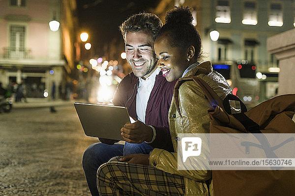 Portrait eines glücklichen jungen Paares mit digitalem Tablet in der Stadt bei Nacht  Lissabon  Portugal