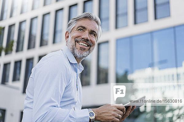 Lächelnder reifer Geschäftsmann mit Tablette in der Stadt