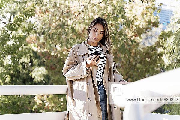Junge blonde Frau benutzt Smartphone