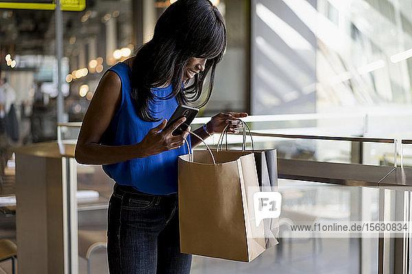 Weibliche Afroamerikanerin benutzt Smartphone beim Einkaufen
