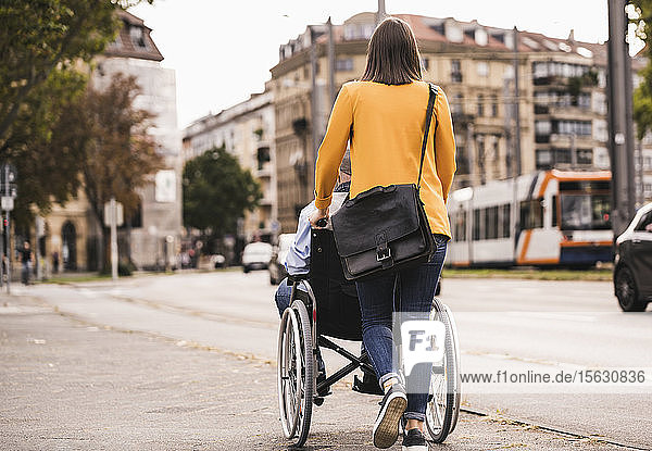 Back view of young woman pushing senior man in wheelchair