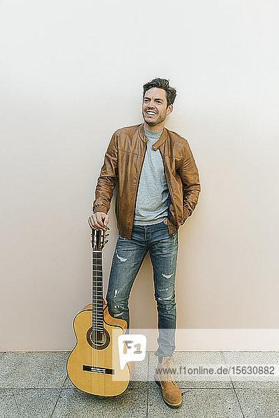 Lächelnder Mann mit Gitarre vor einer Wand